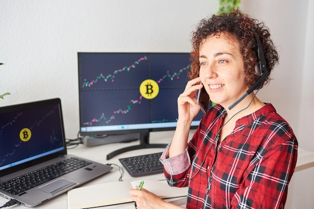 Female trader operates with bitcoins from her standing desk while talking on the mobile phone and wearing a headset