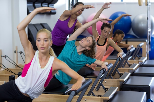 女性のトレーナーがリフォーマーのストレッチ運動で女性のグループを支援