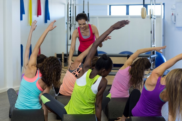 Female trainer assisting group of women with stretching exercise on arc barrel