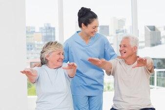 Female trainer assisting senior couple to exercise