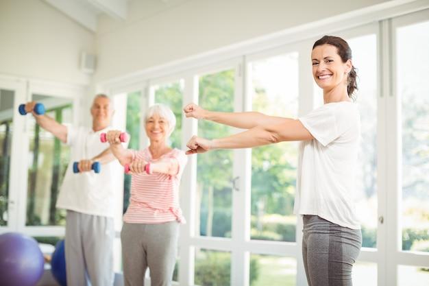 Женский тренер помогает старшим парам в выполнении упражнения