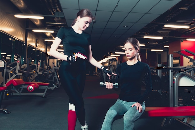 Female trainer assisting woman while exercising with dumbbell
