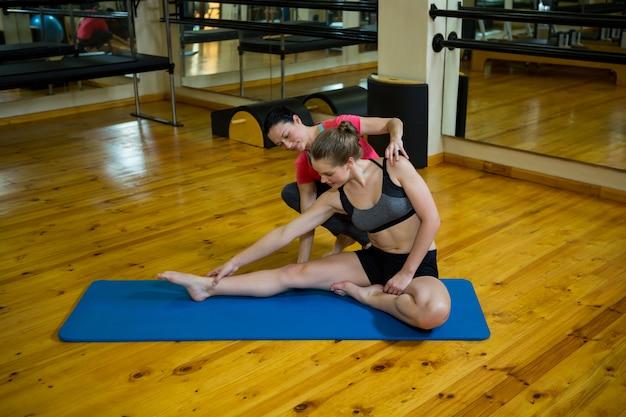 運動で女性を支援する女性のトレーナー