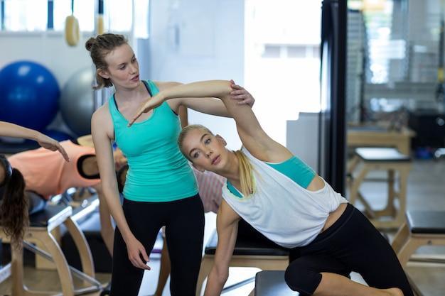 Женский тренер, помогающий женщине с упражнениями
