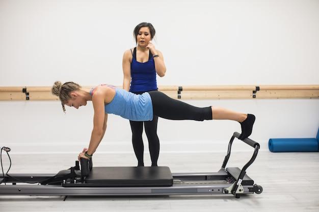 Женский тренер помогает женщине с упражнениями на растяжку на реформаторе