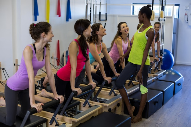 Female trainer interacting with group of women exercising on reformer