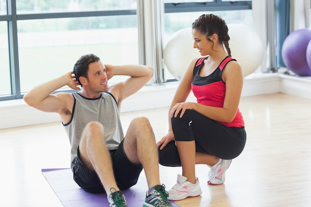 Female trainer looking at man do abdominal crunches