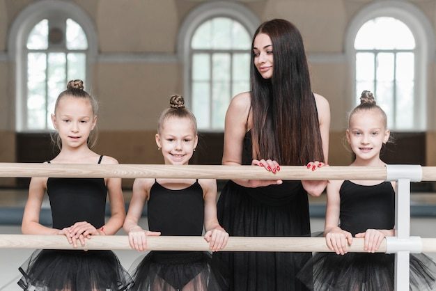 Female trainer looking at three ballerina girls standing behind the barre