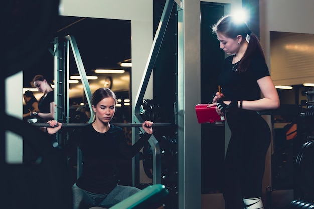 Female trainer looking at woman working out in gym