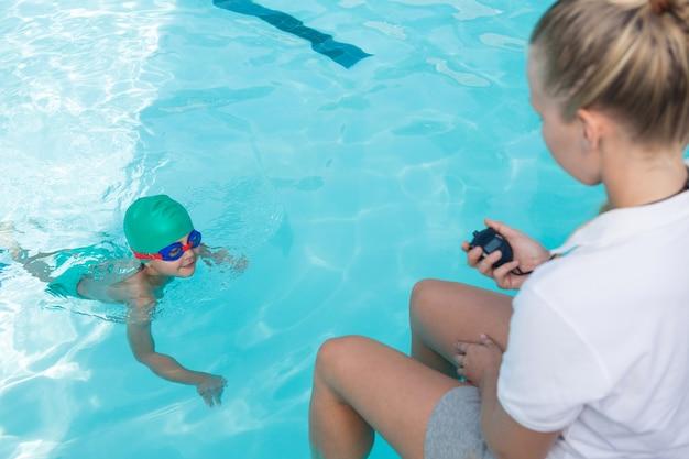 Женский тренер контролирует время плавания мальчика в бассейне