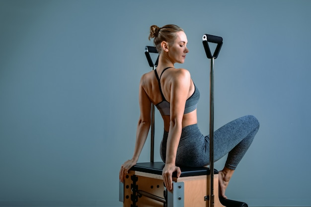 Female trainer posing for a reformer in the gym