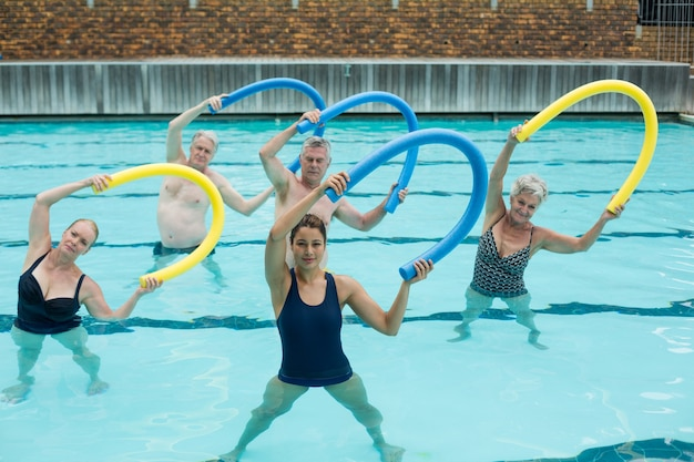 Female trainer and senior swimmers exercising with pool noodle