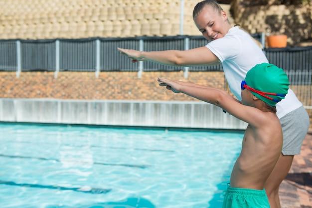 プールに飛び込むための男の子を訓練する女性のトレーナー