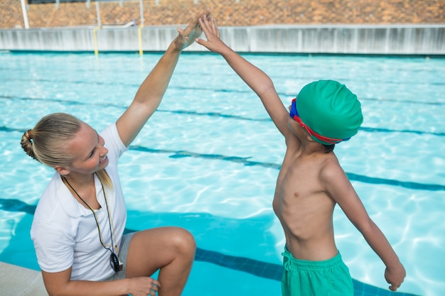 水泳のために少年を訓練する女性のトレーナー