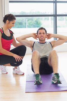 Female trainer watching man do abdominal crunches  on exercise mat