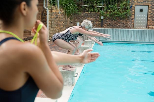 레저 센터에서 수영장에 다이빙하는 노인 여성 동안 휘파람 여성 트레이너