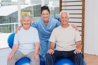 Female trainer with arms around senior couple