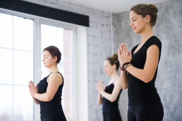 ヨガのクラスでナマステポーズで立っているクラスの女性トレーナー