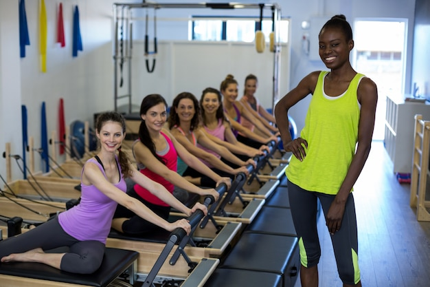 Female trainer with group of women exercising on reformer