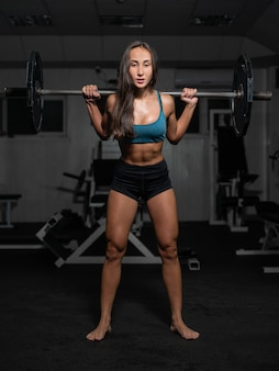Female training with barbell, pumping legs