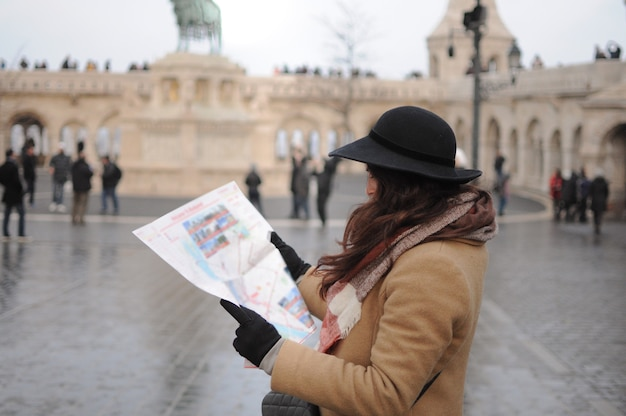 여성 혼자 관광 여행. 여자는 오래 된 도시에서 지도를 봐. 해외 여행.