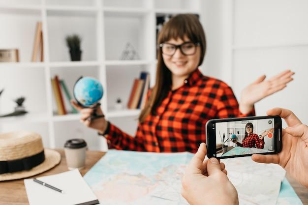 Женский блогер-путешественник, ведущий трансляцию со смартфона дома
