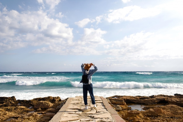 Female traveler admiring a marine view. tourism in cyprus. girl travels on the beaches. young beautiful hipster woman on tropical beach, summer vacation, happy, fun, enjoying, ray of sunshine, sunny.