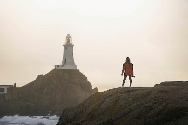 Путешественница на маяке ла корбьер на острове джерси, шотландия