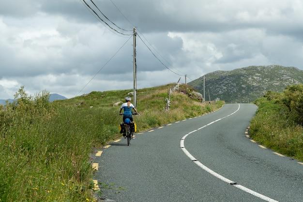 Велосипедистка-путешественница на педалях в горном пейзаже коннемары, голуэй, ирландия