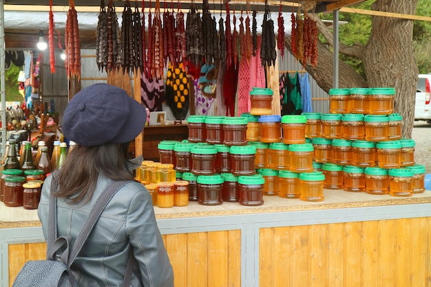 Female traveler in front of a souvenir stand with local products of georgia
