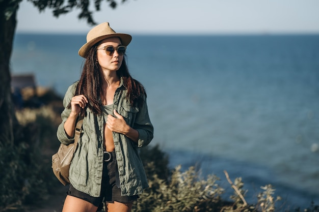 Female traveler in hat and sunglasses with sea behind