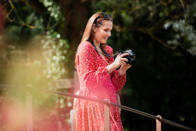 新しい思い出のためのプロのカメラを持っている女性旅行者