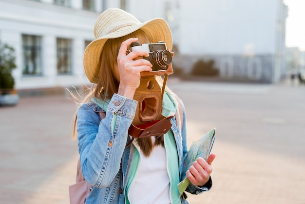 Female traveler holding map in hand taking picture with camera on city street