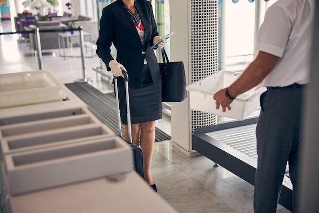 空港労働者が彼女の荷物のための女性の箱を提供している間、チケットと旅行スーツケースを保持している滅菌手袋の女性旅行者