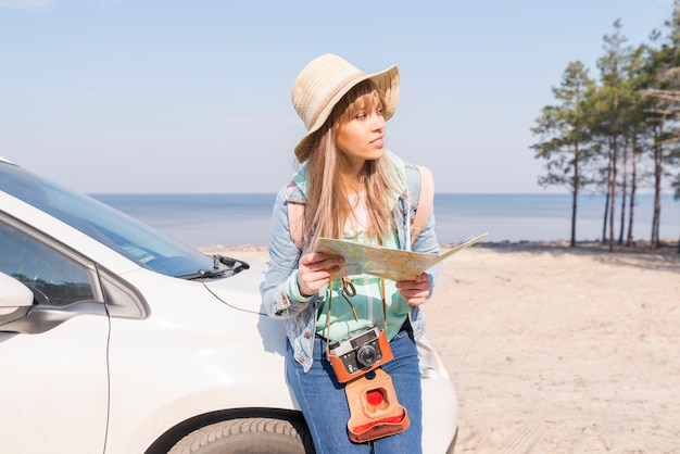 Female traveler leaning near the white car holding map in hand looking away