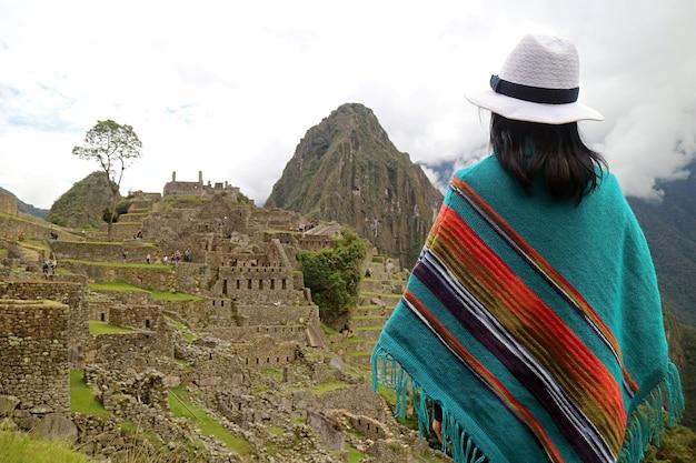 Female traveler looking at the ancient citadel of machu picchu, in cusco region of peru