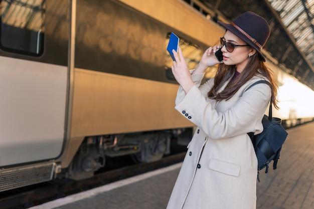 Female traveler looks in passport and talks on mobile phone
