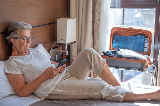 A female traveler lying on the bed in the hotel room using her cellphone. the open suitcase and a large window behind hrt