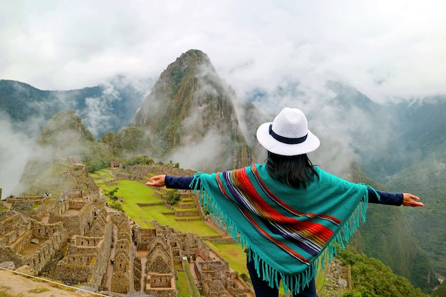 Female traveler opening arms to ancient inca citadel of machu picchu, cusco region of peru