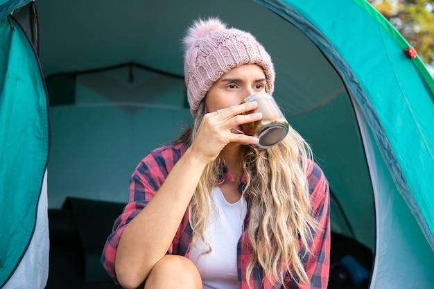 テントに座ってお茶を飲む女性旅行者。帽子をかぶって、自然にキャンプし、目をそらし、景色を楽しむ白人のブロンドの女性。観光、冒険、夏休みのコンセプトをバックパッキング