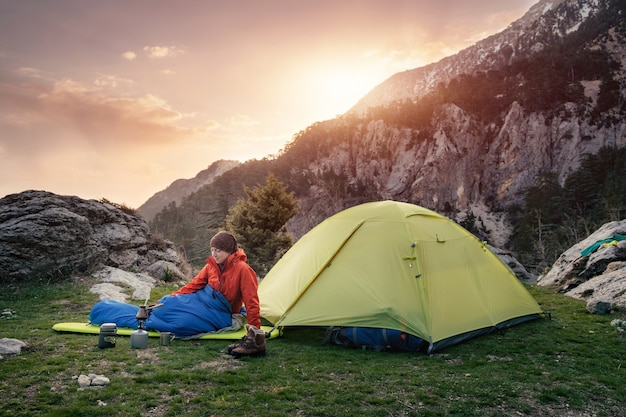 Female traveler in sleeping bag near the tent in the mountains