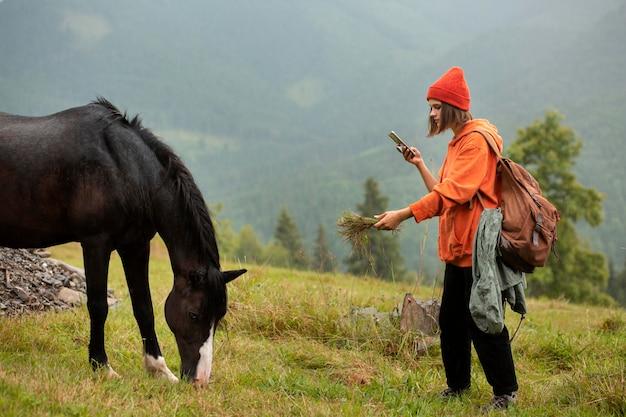 Путешественница пытается кормить лошадь