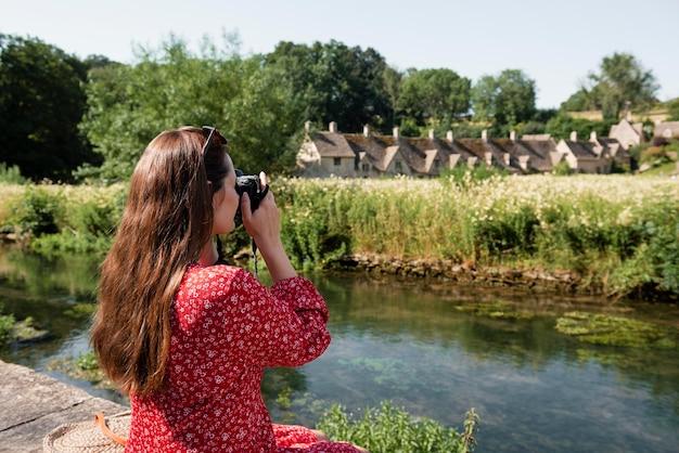 新しい思い出のためにプロのカメラを使用している女性旅行者