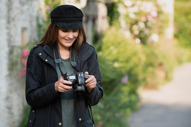 Viaggiatrice che utilizza una fotocamera professionale per nuovi ricordi