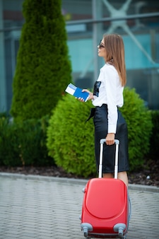 Female traveler walking with their luggage near airport