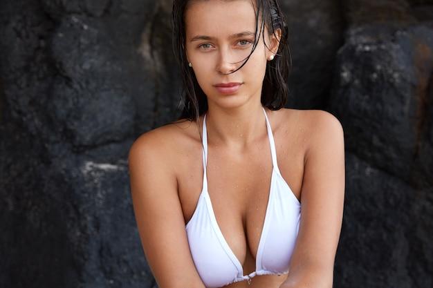 Female traveler in white bikini poses against rock, has dark long wet hair