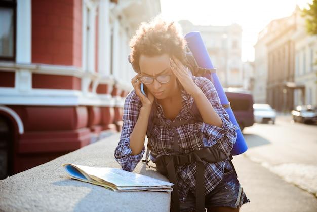 Женский путешественник с рюкзаком, говоря по телефону, глядя на карту.