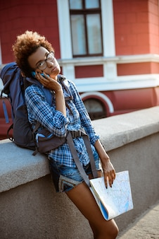 Female traveler with backpack speaking on phone, holding map.