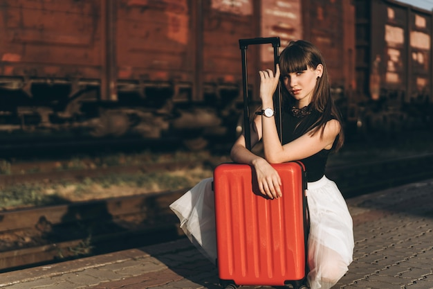 Female traveler with red suitcase waiting train on railway station