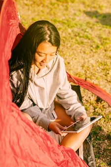 Female traveler with tablet sitting in tent